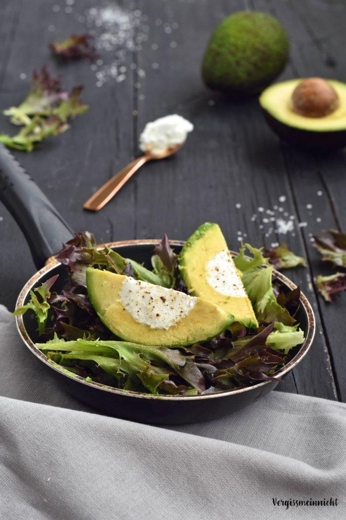 Gefüllte Avocado mit Ziegenkäse auf Salat angerichtet